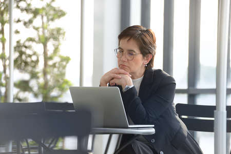 1 person: Executive businesswoman  working with laptop computer at outdoor cafe Stock Photo