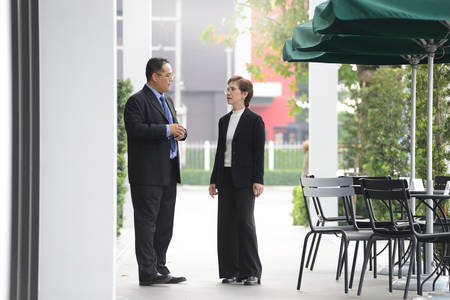 Businessman and businesswoman discussing and working together during a meeting outside office Stock Photo