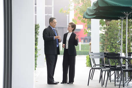project: Businessman and businesswoman discussing and working together outside office
