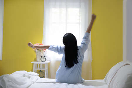 Woman stretching in bed after wake up, back view Banco de Imagens