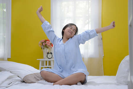Young teenage girl stretching in bed after wake up Stock Photo