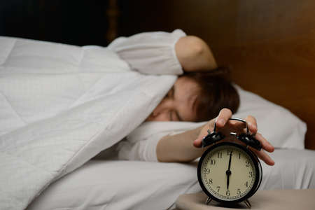 bedroom: Young woman turning off the alarm clock on the bed