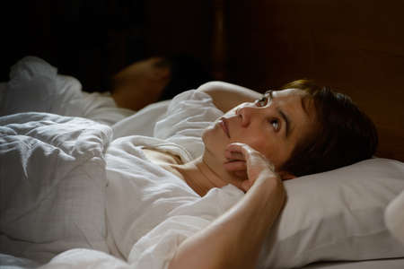 bedroom: Woman with insomnia lying in bed with open eyes