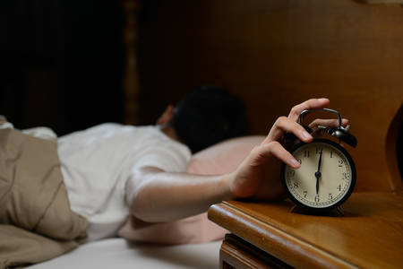 Young man turning off the alarm clock on the bed Stock Photo