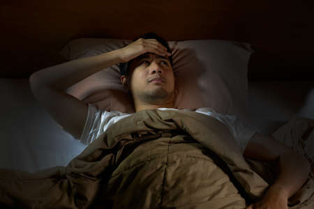 bedroom: Depressed man suffering from insomnia lying in bed Stock Photo
