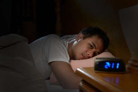 Depressed man suffering from insomnia lying in bed Stockfoto