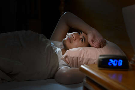 침대에 누워있는 불면증으로 고통받는 우울한 남자 스톡 콘텐츠