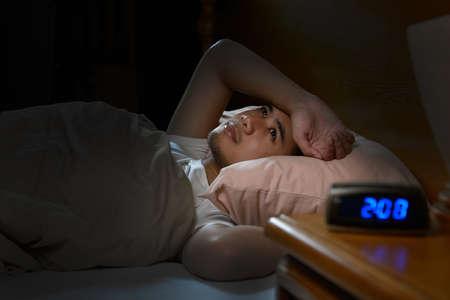 Gedeprimeerde man die lijdt aan slapeloosheid in bed liggen Stockfoto