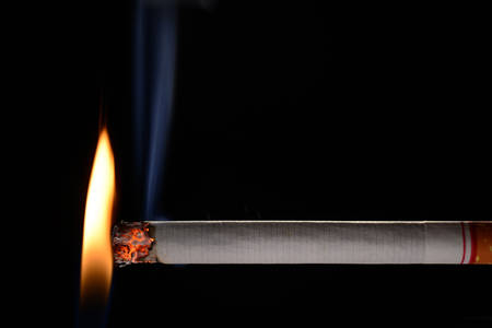 Cigarette being lit by small flame on black background Stock Photo