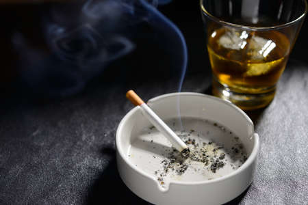 Lit and smoking cigarette in ashtray with glass of whiskey Banque d'images