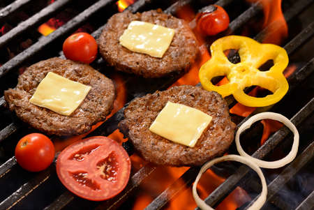 Grilled meatburger with cheese on top and vegetable on the flaming grill