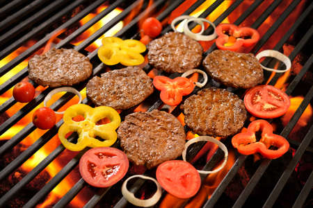 Grilled meatburger with vegetable on the flaming grill Stock Photo