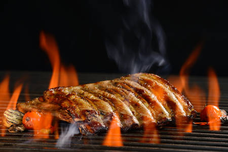 Grilled pork ribs with vegetable on the flaming grill       Stock Photo