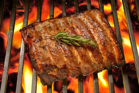Grilled pork ribs on the flaming grill Stock Photo