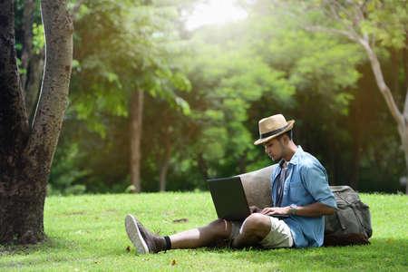 Jonge mens die en aan laptop in het park reist werkt