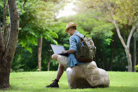 Young man traveling and working on laptop in the park