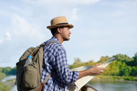 Young Asian tourist man with backpack and map looking at the nature
