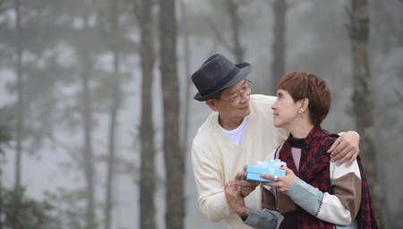Happy senior man surprises wife with present outdoor