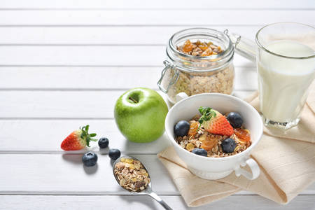Healthy food, healthy muesli breakfast with milk and fruits on white wooden table Stock Photo
