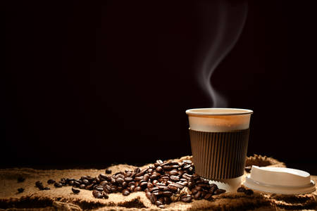 Paper cup of coffee with smoke and coffee beans on black background Stock Photo