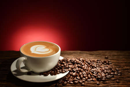 Cup of coffee latte and coffee beans on reddish brown background Stock Photo - 96494057
