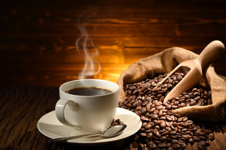 Cup of coffee with smoke and coffee beans on old wooden background 免版税图像