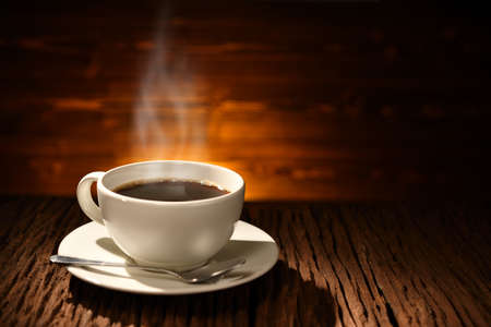 Cup of coffee with smoke on old wooden background Фото со стока - 97486571