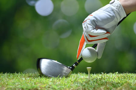 Hand hold golf ball with tee on golf course Stockfoto