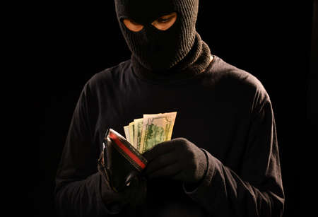 Thief taking the money from stolen wallet Stock Photo