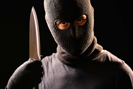The robber hold the knife in hand on black background Stock Photo