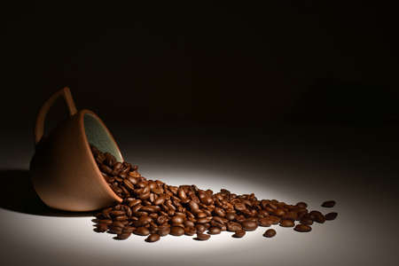 Coffee beans in coffee cup in spotlight on dark background Reklamní fotografie