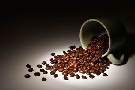 Coffee beans in coffee cup in spotlight on dark background Stock Photo