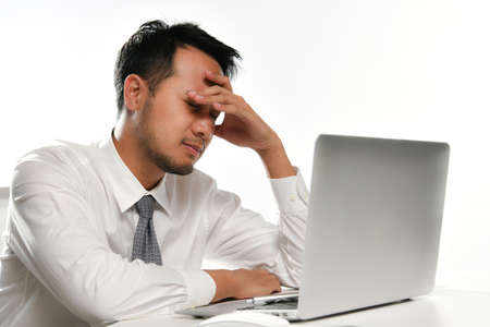 Stressed business man covering his face with his hand while working on a computer in the office Stock Photo
