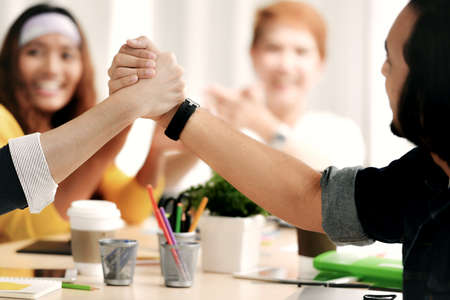 Image of 2 persons firmly holding hands in agreement in meeting at office