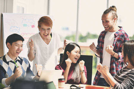 Group of businesspersons feeling happy and cheering successful work on screen Stock Photo