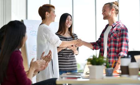 Two businesspersons shaking hands in agreement with congratulating colleagues