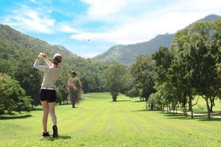 Joven mujer asiática jugando al golf en un hermoso campo de golf natural Foto de archivo