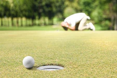 Mann-Golfer, der enttäuscht ist, nachdem ein geputterter Golfball das Loch verfehlt hat Standard-Bild