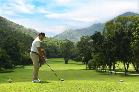 Young man playing golf on a beautiful natural golf course Imagens