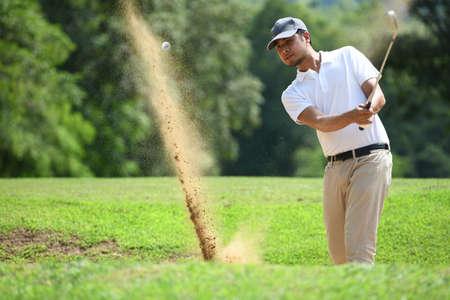 Young Asian man golfer hitting a bunker shot Stok Fotoğraf