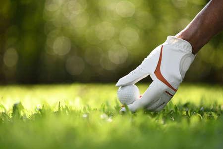 Asimiento de la mano con la pelota de golf tee en campo de golf