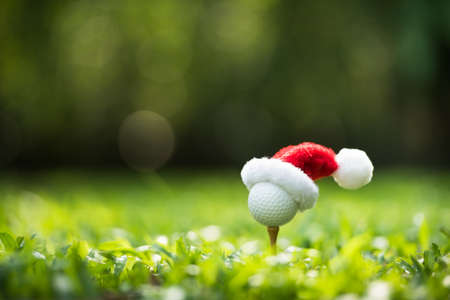 Festive-looking golf ball on tee with Santa Claus' hat on top for holiday season on golf couse backgroubd