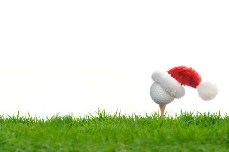 Festive-looking golf ball on tee with Santa Claus' hat on top for holiday season isolated on white background Stock Photo