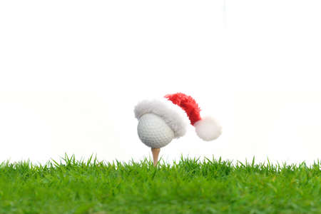 Festive-looking golf ball on tee with Santa hat on top for holiday season isolated on white background