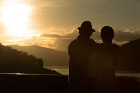 Image of sunset on orange and yellow horizon with a silhouette of a senior couple in natural surrounding Archivio Fotografico