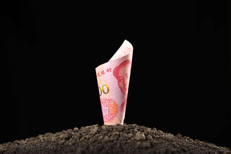 Image of China Yuan banknote on top of soil for business, saving, growth, economic concept isolated on black 스톡 콘텐츠
