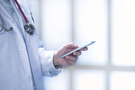 Medical doctor using smart phone for work in hospital Stock Photo