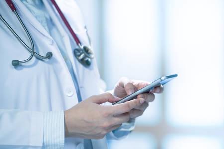Docteur en médecine utilisant un téléphone intelligent pour travailler à l'hôpital