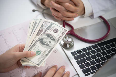 Patient giving money to medical doctor in hospital setting