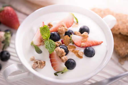 Top view of plain yogurt with fresh fruits and granola on top in bowl on the table
